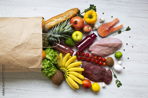 Fotografiet Paper bag of healthy products on white wooden background, top view