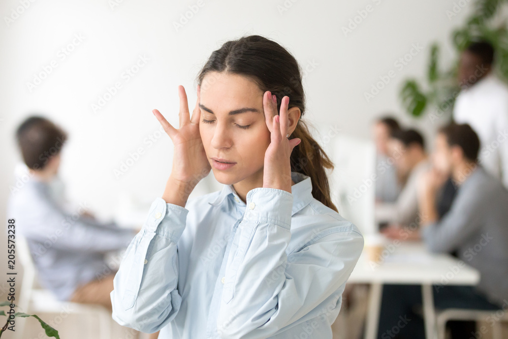 Fototapeta Stressed frustrated young woman employee feeling pain unwell dizzy, tired of difficult office job, suffering from panic attack, hormone imbalance or having headache migraine massaging temples at work
