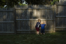 Rear View Of Brothers Peeking Through Wooden Fence While Playing At Backyard