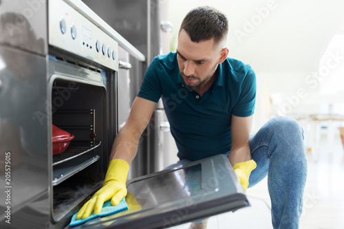 Cuadros en Lienzo household and people concept - man wiping table with cloth cleaning oven door at