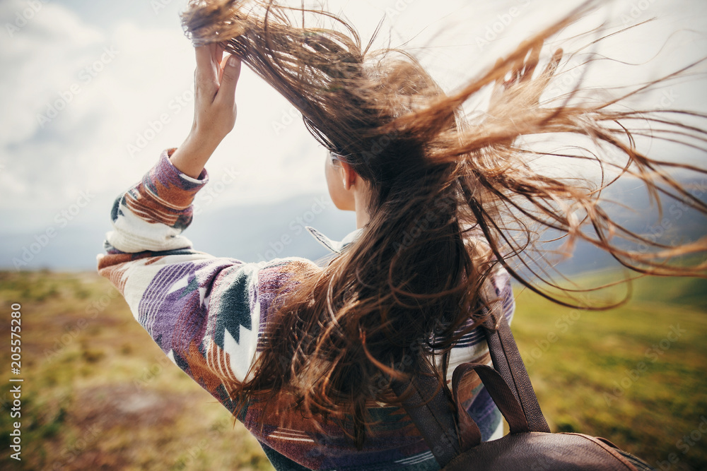 Fototapety, obrazy: traveler hipster girl with windy hair and backpack, standing on top of sunny mountains. space for text. stylish woman waving hair. atmospheric moment. travel and wanderlust concept.