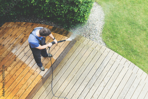 Fotografia  man cleaning terrace with a power washer - high water pressure cleaner on wooden
