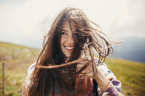 Fototapeta  happy traveler hipster girl with windy hair and smiling, standing on top of sunny mountains