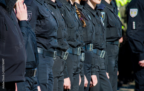 Tela Female police officers in black uniform standing in a row
