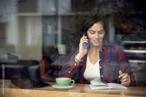 Woman talking on smart phone while sitting in cafe seen through window