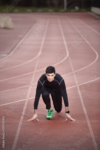 Portrait of confident athlete at starting line