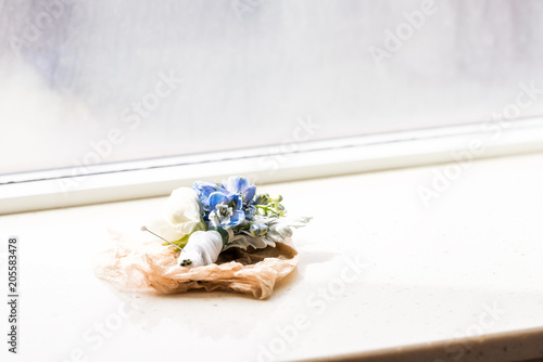 One wedding flower boutonniere lying with pin on windowsill