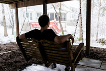 Young Man Sitting On Swing Under Wooden Deck Of House On Backyard In Neighborhood With Snow During Blizzard White Storm, Snowflakes Falling In Virginia Suburb, Single Family Home
