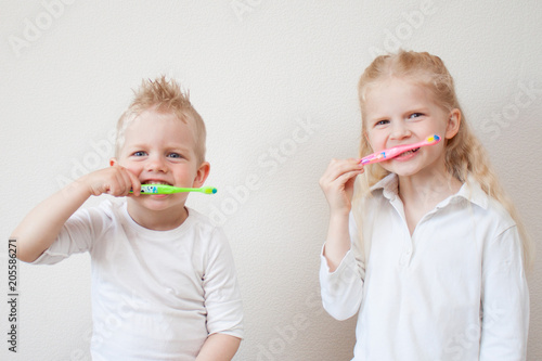 Photo Stands Grocery Adorable little blonde girl and boy with tooth brushes. Fun home play. Children smile. Healthy lifestyle, not afraid of dentist office. Health care, dental hygiene