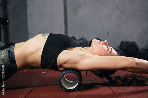 Beautiful young caucasian woman sportswoman uses a foam roller massager for relaxation, stretching muscles and back pain. Girl in the gym green sneakers T-shirt and tights