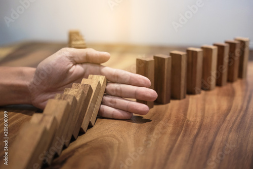 Valokuva  Risk and strategy in business, Close up of businessman hand stopping wooden bloc