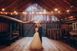 canvas print picture - stylish groom and happy bride hugging under retro bulbs lights in wooden barn. rustic wedding concept, space for text. newlyweds couple embracing, sensual romantic moment
