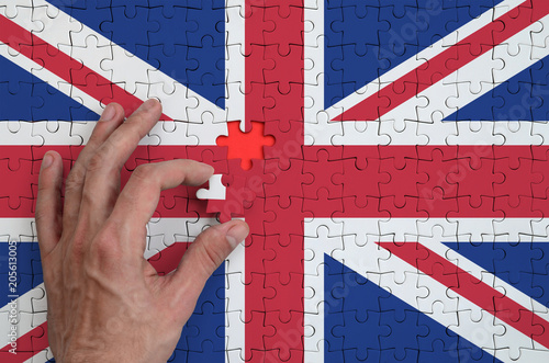 Poster  Great britain flag  is depicted on a puzzle, which the man's hand completes to f