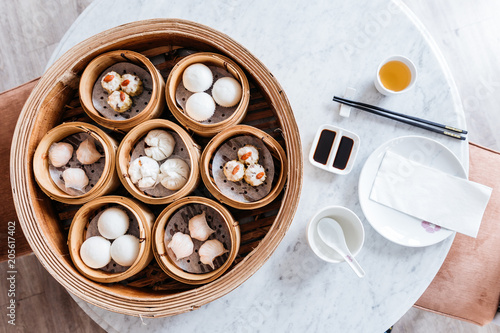 Top view of Dim sum set: Barbecued pork bun, Shrimp dumpling, Sweet cream buns, Shrimp shumai topping with goji berry served in steamer baskets with plate, chopsticks, sour sauce and hot tea.