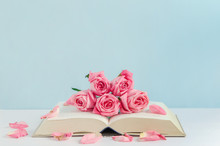 Vintage Pink Rose Flowers With Book On White And Blue Wooden Background