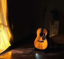 Acoustic Spanish Guitar On A Stand In The Moody Shadows Of A Dark Room With Bright Light Coming In From Behind A Curtain