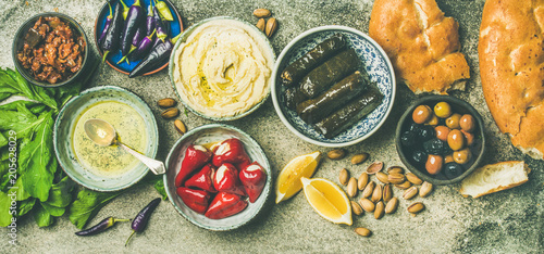 Mediterranean, Middle Eastern meze starter platter. Stuffed pickled paprikas, dolma, hummus, spiced oil, olives, sundried tomatoes, nuts, lemon, flatbread over concrete background top view