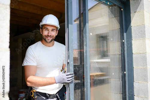 Obraz handsome young man installing bay window in new house construction site - fototapety do salonu