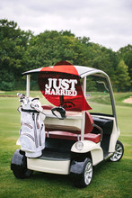 Just Married Sign On Red Heart On Empty Golf Car Outdoors. Wedding Concept. Golf Cart On Golf Course, Copy Space. Golf Club