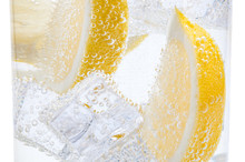 In A Glass With Cubes Of Melting Ice Slices Of A Juicy Yellow Lemon.