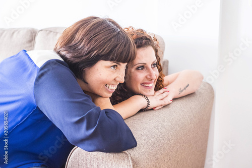 couple od two women friends stay close together on the sofa smiling and having fun. friendship or relationship at home indoor with nice lifestyle way to live concept
