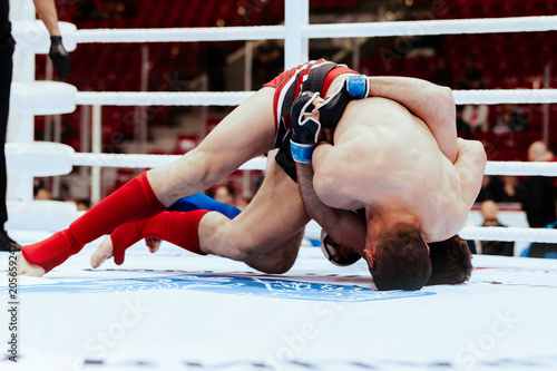 two MMA fighters fight on floor ring competition in martial arts