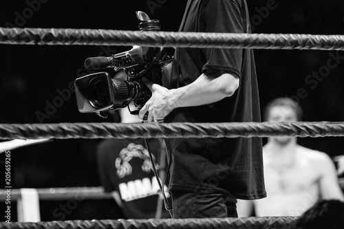 Photo  cameraman with video camera in ring during competition MMA black and white photo