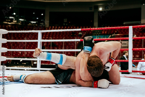 Foto op Plexiglas Vechtsport MMA fight two fighters on floor ring competition in martial arts