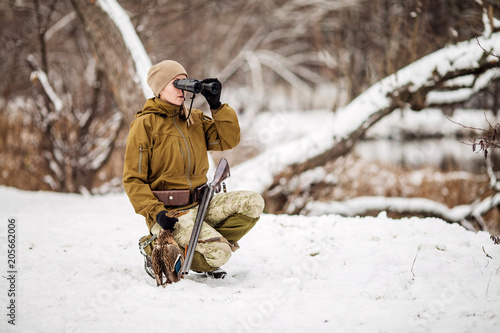 Foto op Aluminium Jacht Female hunter in camouflage, armed with a rifle, standing in a snowy winter forest with duck prey