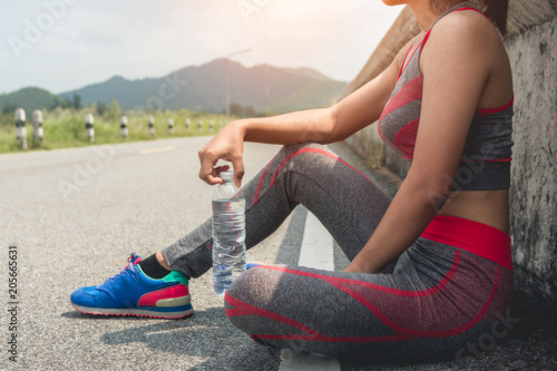 Fotobehang Ontspanning Sporty woman sitting and resting after workout with shake or drinking water on floor. Relax concept. Strength training and Body build up theme. Warm and cool tone
