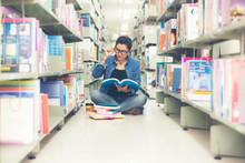 Asian Women In Library Reading Something In A Book And Choosing A Book In A Library.  Education  Concept
