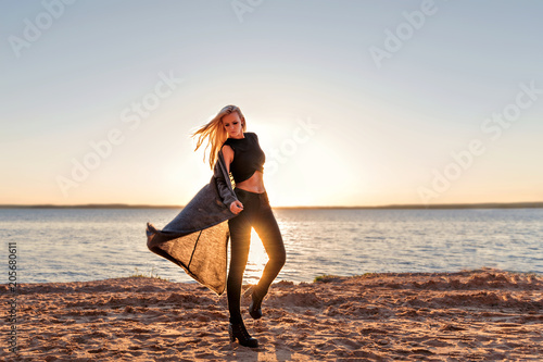 A girl of a sporty body steps into the dance and walks along the sandy beach at Wallpaper Mural