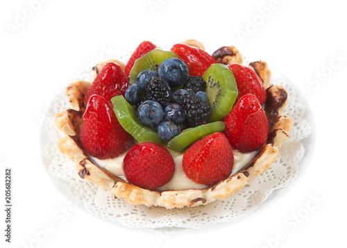 Fotografia, Obraz  Fresh summer fruit tart with strawberries, kiwi, blueberries, boysenberries on a white doily on plate isolated on white background