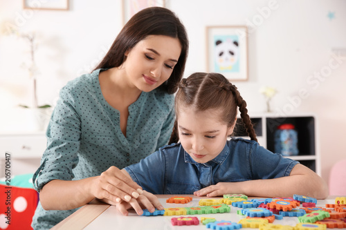 Young woman and little girl with autistic disorder playing at home Canvas Print