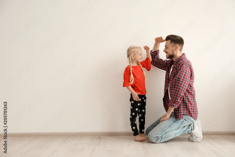 Fototapety, obrazy: Young man and little girl measuring their height indoors