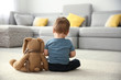 canvas print picture - Little boy with toy sitting on floor in living room. Autism concept