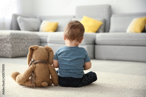 little-boy-with-toy-sitting-on-floor-in-living-room-autism-concept