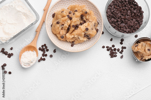 Foto auf Leinwand Kekse Flat lay composition with cookie dough, chocolate chips and flour on light background