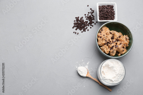 Foto op Plexiglas Koekjes Flat lay composition with cookie dough, chocolate chips and flour on grey background