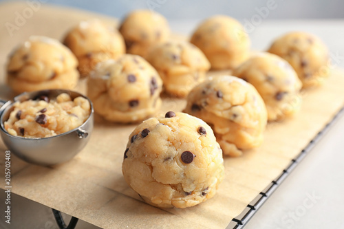 Raw cookie dough with chocolate chips and scoop on parchment paper, closeup