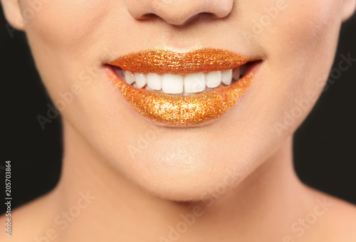 Foto op Plexiglas Beauty Beautiful young model with golden lips makeup on black background