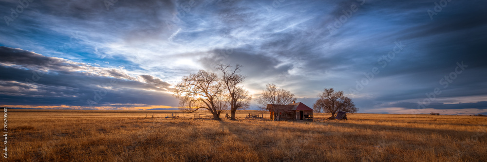 Fototapeta Old farmhouse at sunset in the countryside