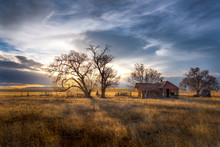 Old Farmhouse At Sunset In The Countryside