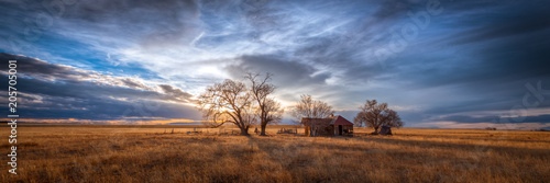 Fotomural Old farmhouse at sunset in the countryside