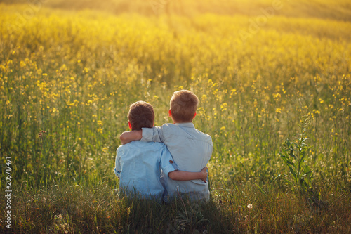 Fotografía  Two little boys friends holding around the shoulders in sunny summer day