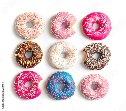 Delicious doughnuts with sprinkles on light background, top view