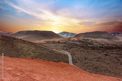 Fotografia  A road crossing the Timanfaya National Park at sunset