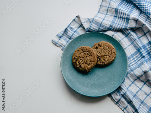 Staande foto Koekjes Cookie with chocolate chips Homemade cookies are lying on a blue plate with checkered tablecloth Top view photo with copy space