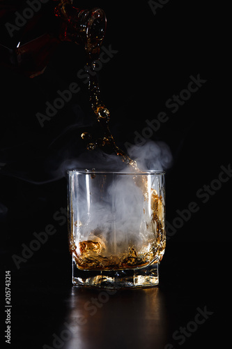 Foto op Aluminium Alcohol a glass of whiskey, rum or alcohol on a dark background