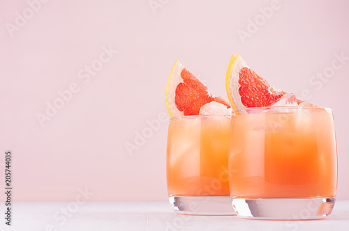In de dag Cocktail Cold grapefruit cocktail in two glasses with ice and pieces grapefruit on pastel pink background. Fresh summer healthy diet beverage.